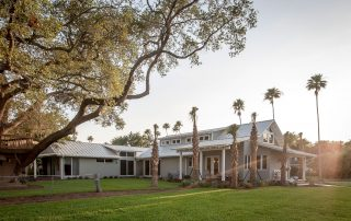 Gray and white home with large oak tree and row of palms in front