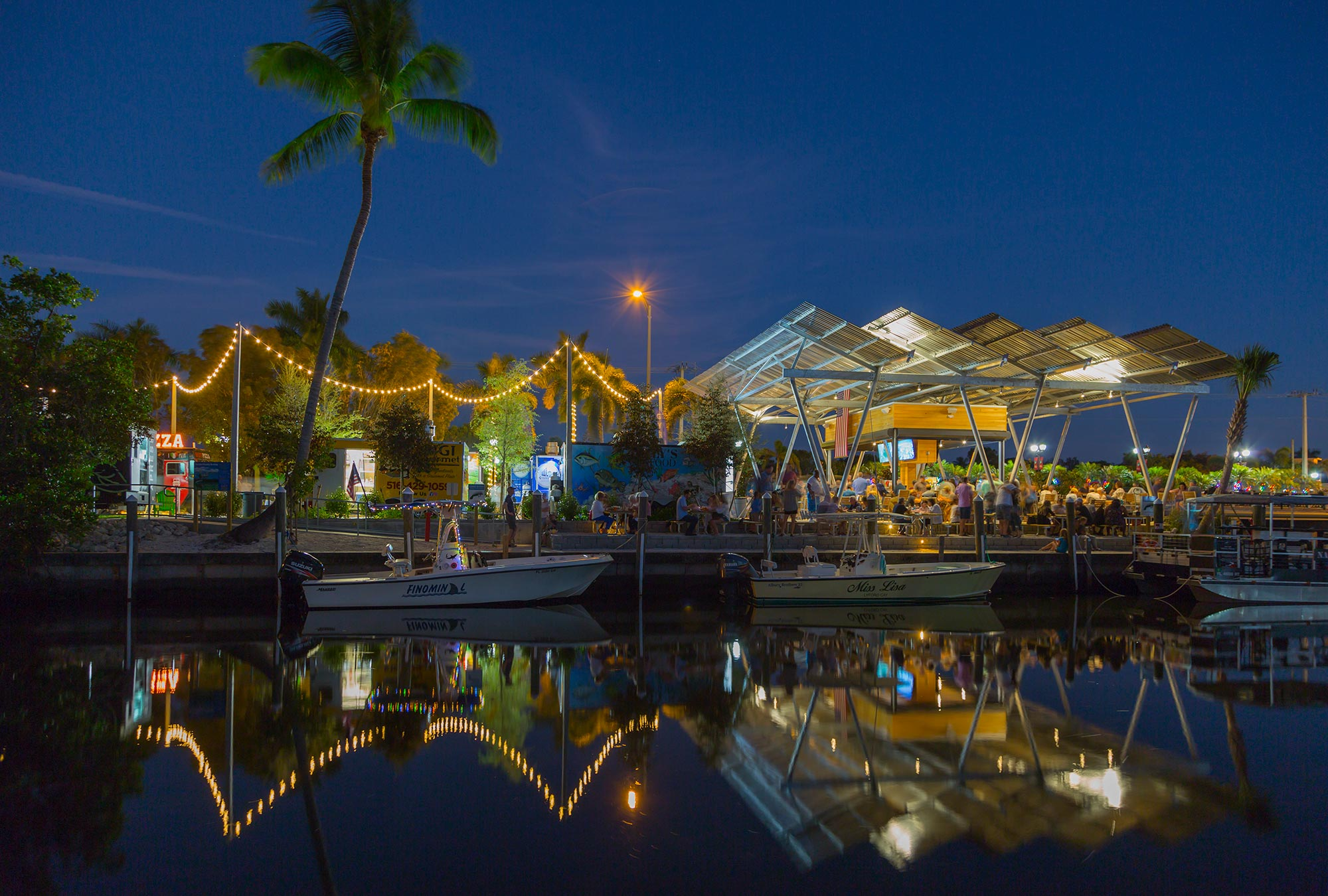 Food truck park from across the water at night.