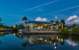 Tiki bar from across the water at dusk.