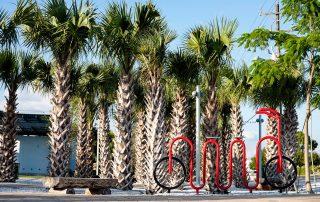 Custom bike rack with palm trees beyond.