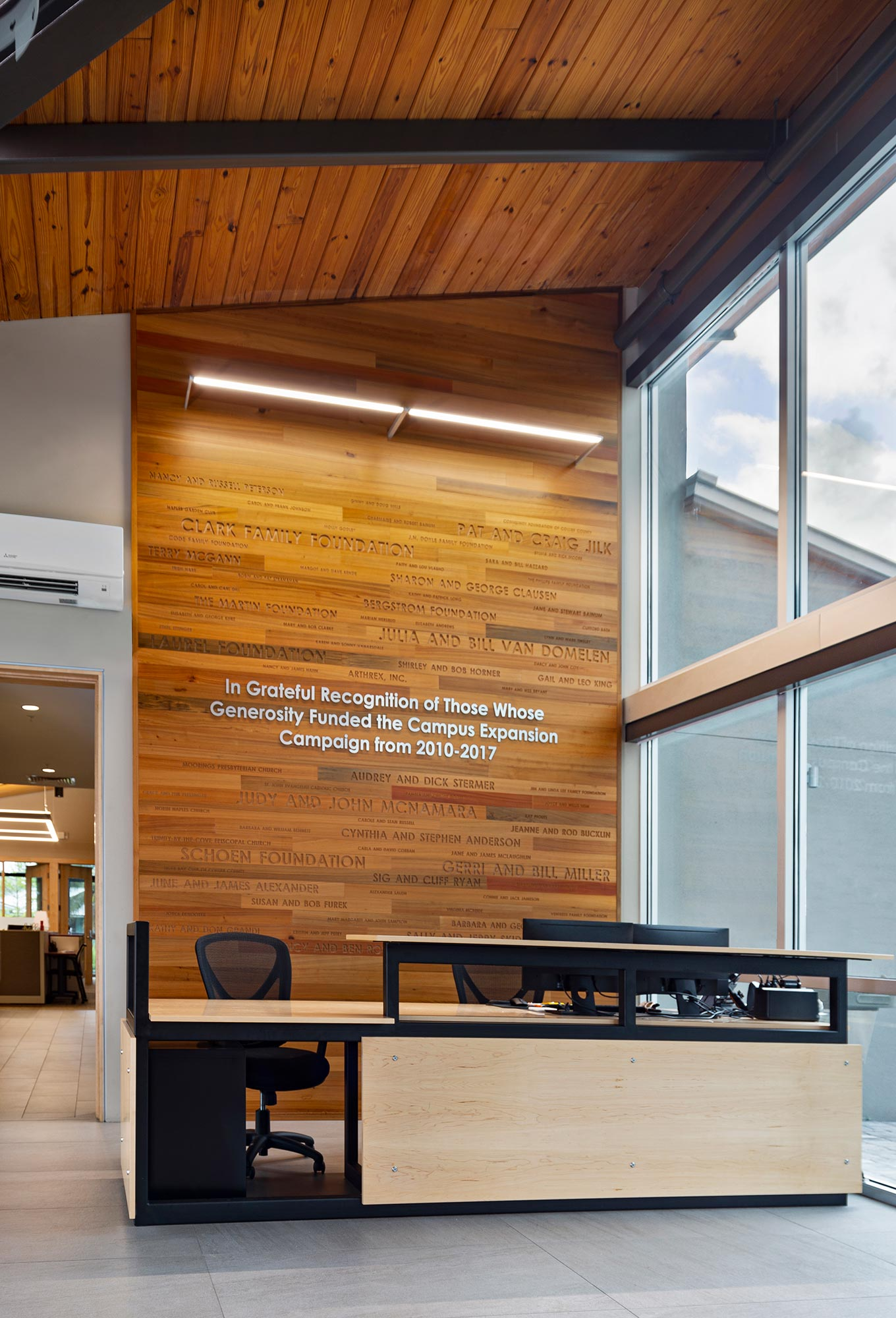 Reclaimed cypress donor wall and reception desk designed by architect.