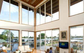 Double height living room space with large windows and natural light.