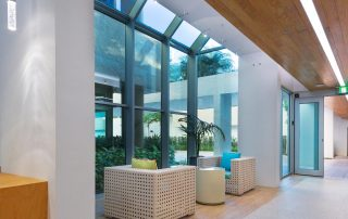 Interior lobby with modern furniture and skylight beyond.
