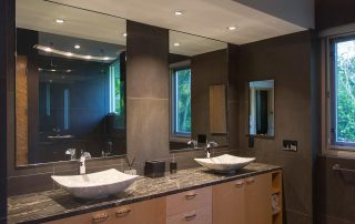 Master bath with custom wood cabinetry and modern fixtures.