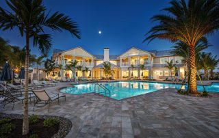 Resort style pool deck with clubhouse beyond.