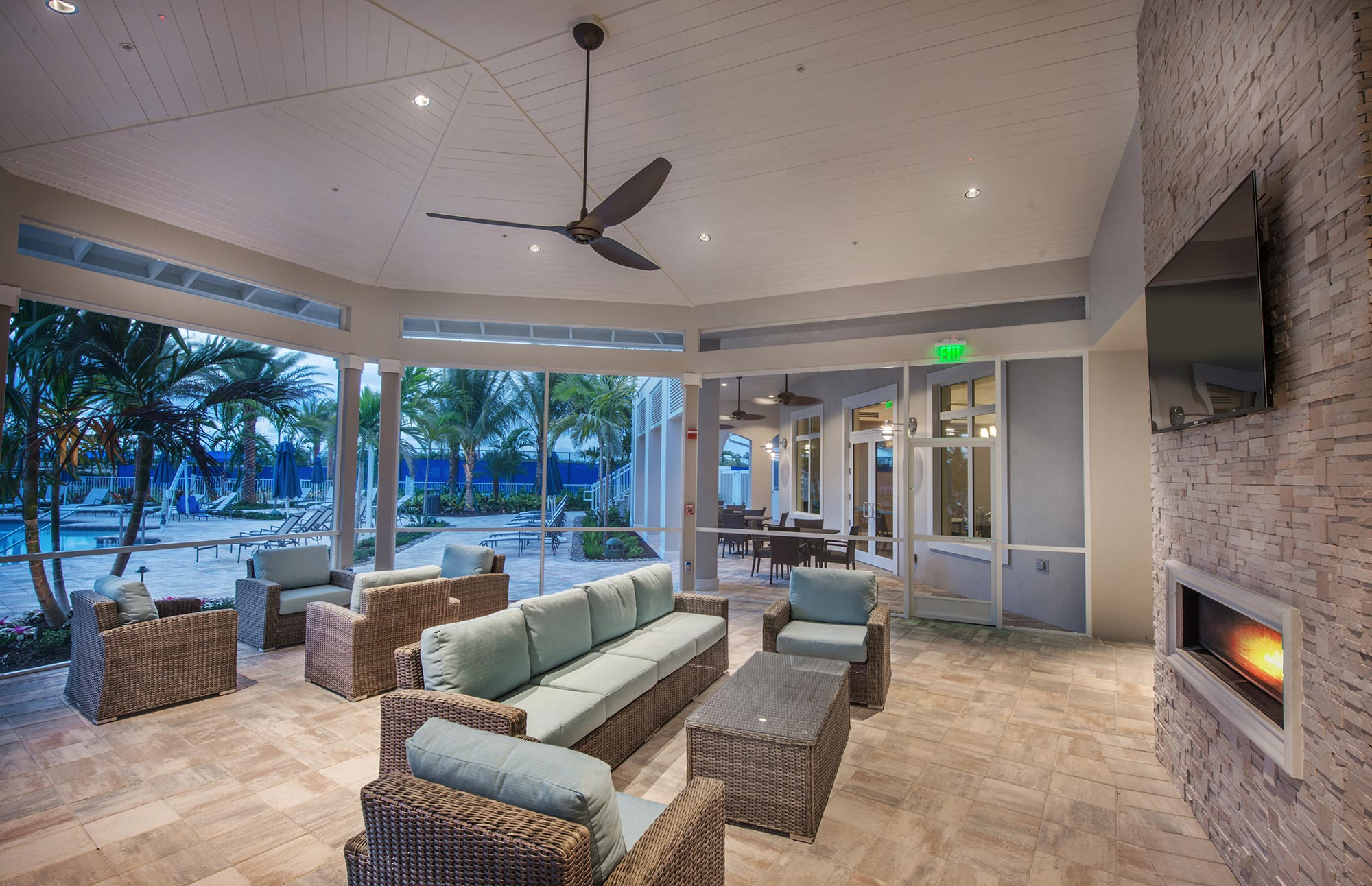 Screened porch with fireplace and pool deck beyond.