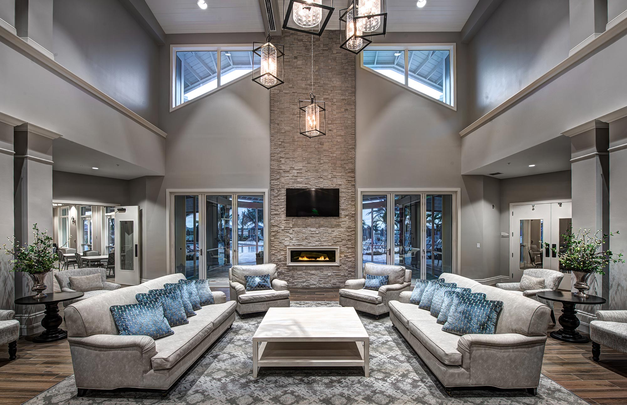 Clubhouse common area with tall ceilings, fireplace, and comfy couches.